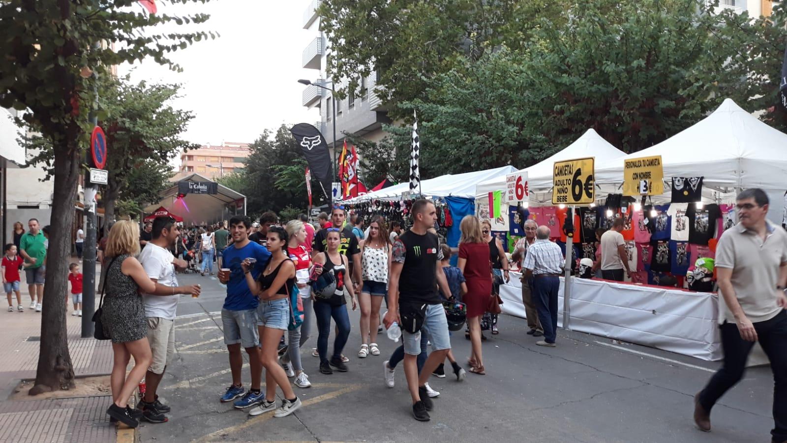 Ambiente en la avenida llena de stands de merchandising el viernes por la tarde
