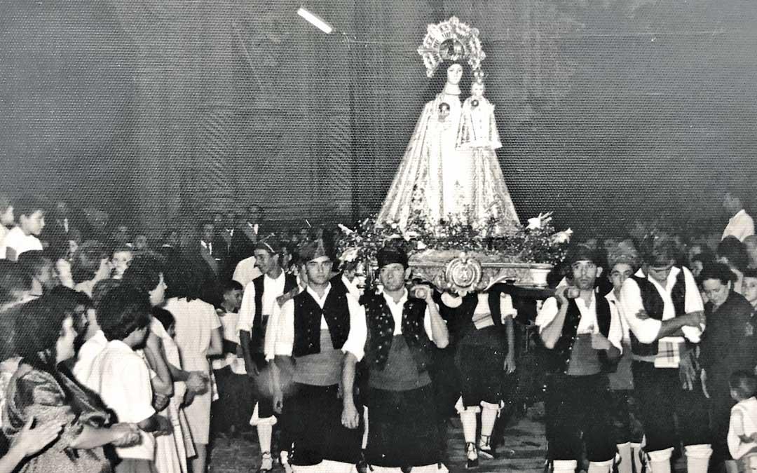 La Virgen de Pueyos portada por baturros entre la multitud saliendo de misa en la ex colegiata Santa María la Mayor el año 1962. Foto: Archivo Municipal de Alcañiz