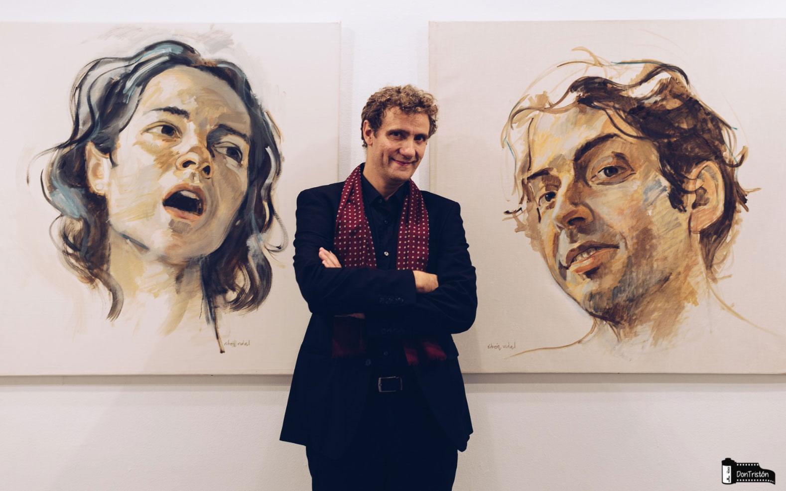 El pintor Rubén Vidal junto a dos retratos de gran formato en el Centro Joaquín Roncal de Zaragoza