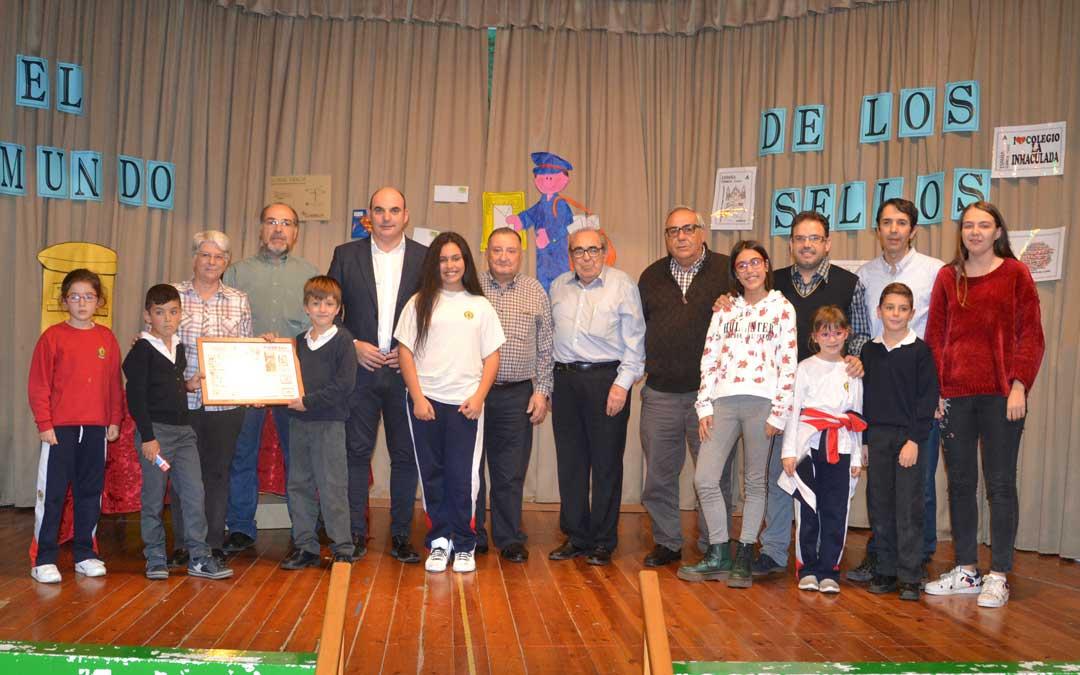 Foto de familia de los alumnos ganadores de los dos concursos junto con la dirección del colegio, la asociación Filatélica de Alcañiz y el alcalde, este jueves. l. castel