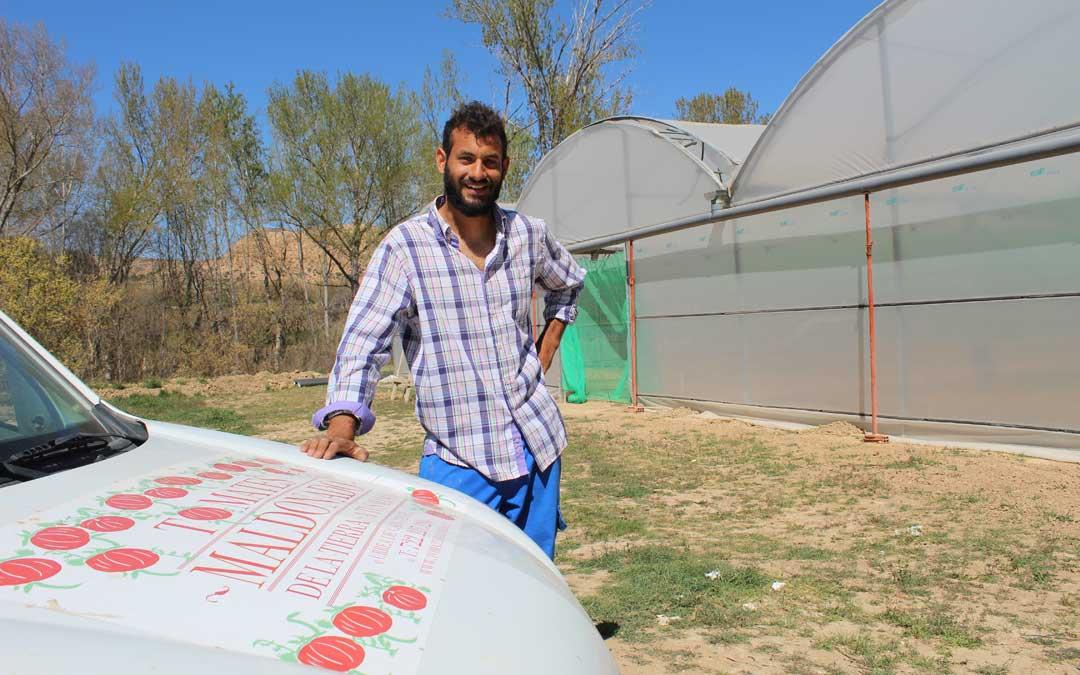 Carlos, con su furgoneta y su invernadero en el que crece su proyecto en Urrea, localidad a la que llegó desde Argentina