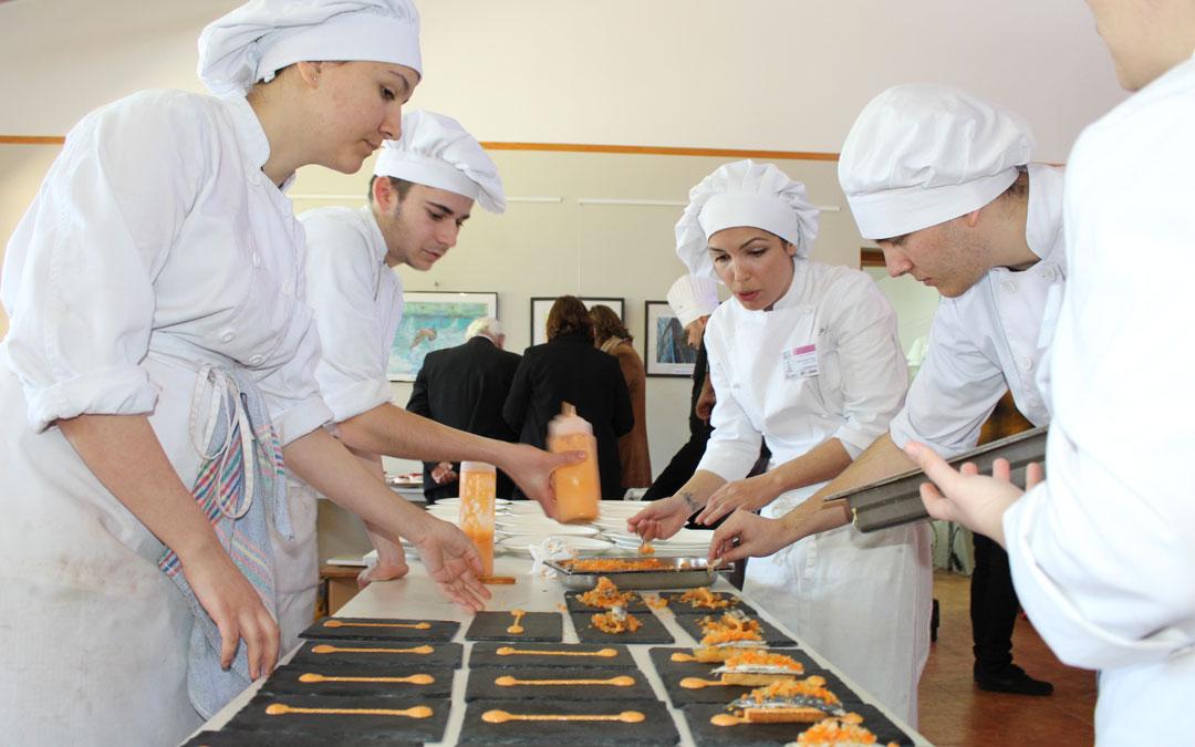 Alumnos del centro andorrano, ultimando el aperitivo para servir. Al fondo, las autoridades reciben explicaciones. / B. Severino