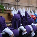 Los cofrades cargan con una de las penas durante la procesión de la Soledad.