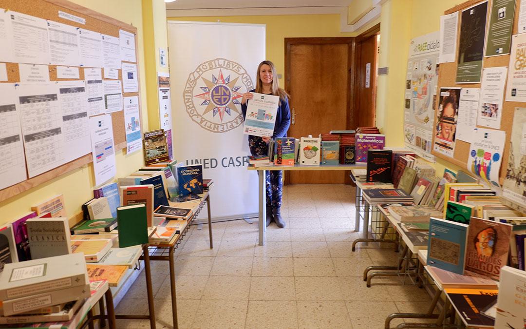 Merche Catalán, secretaria de UNED Caspe, junto a los libros donados.