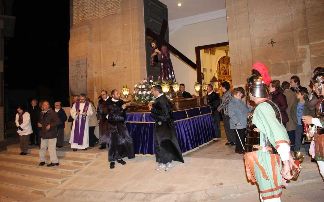 Salida del Nazareno de la iglesia de Urrea de Gaén arropado por los rosarieros y alabarderos que lo acompañaron a la plaza para el Encuentro.