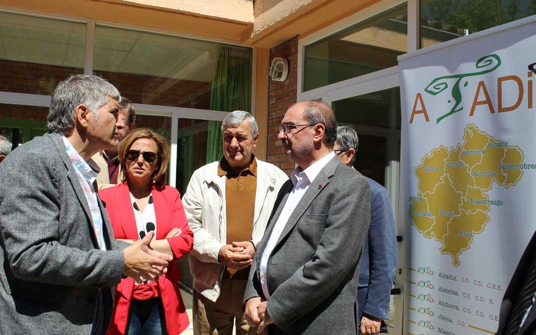 Javier Lambán y Mayte Pérez atienden las explicaciones de Mora en la entrada de ATADI en Alcañiz. / B. Severino