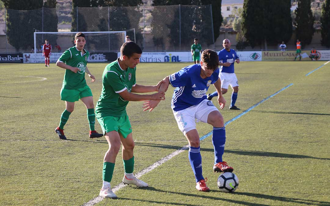 El jugador del Caspe Javier Muniesa controla un balón ante la oposición del rival