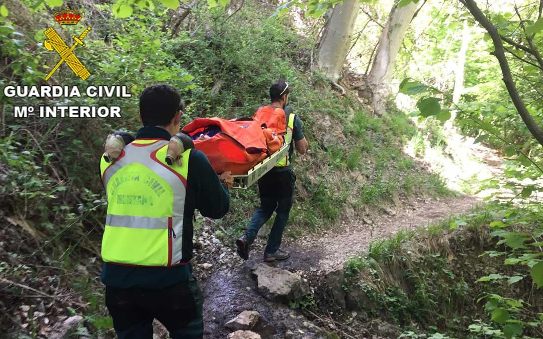 Dos agentes de la Guardia Civil cargaron con el herido en una camilla hasta un lugar de fácil acceso para el helicóptero
