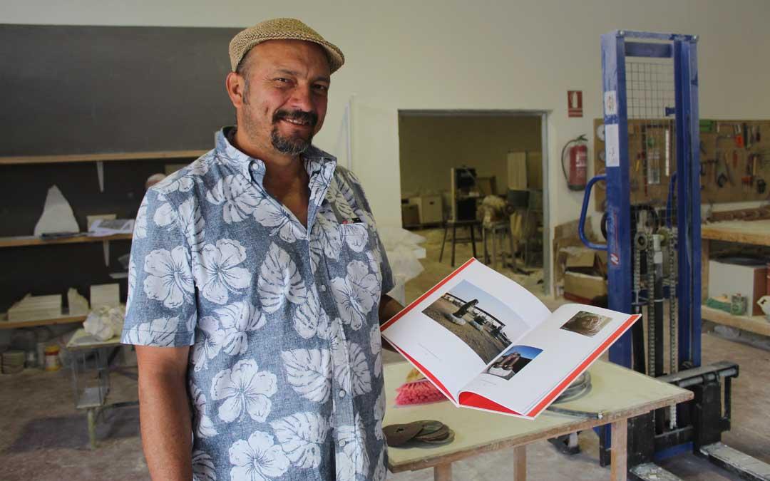 Marco Cueva, mostrando su 'book' con su instalación en granito en Albalate en su itinerario de vacaciones para visitar el workshop de Beccari. / B. Severino