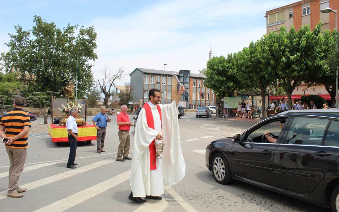 El cura párroco de Caspe, en plena bendición de los vehículos por San Cristóbal. / B. Severino