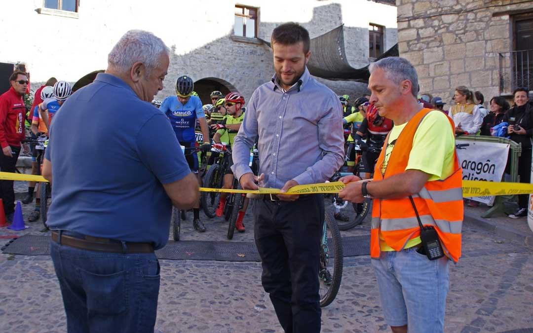 El presidente del Maestrazgo, Roberto Rabaza, cortó la cinta con el alcalde, Luis Gil, y el director de la prueba, Ángel Zaera. / BTT Fortanete
