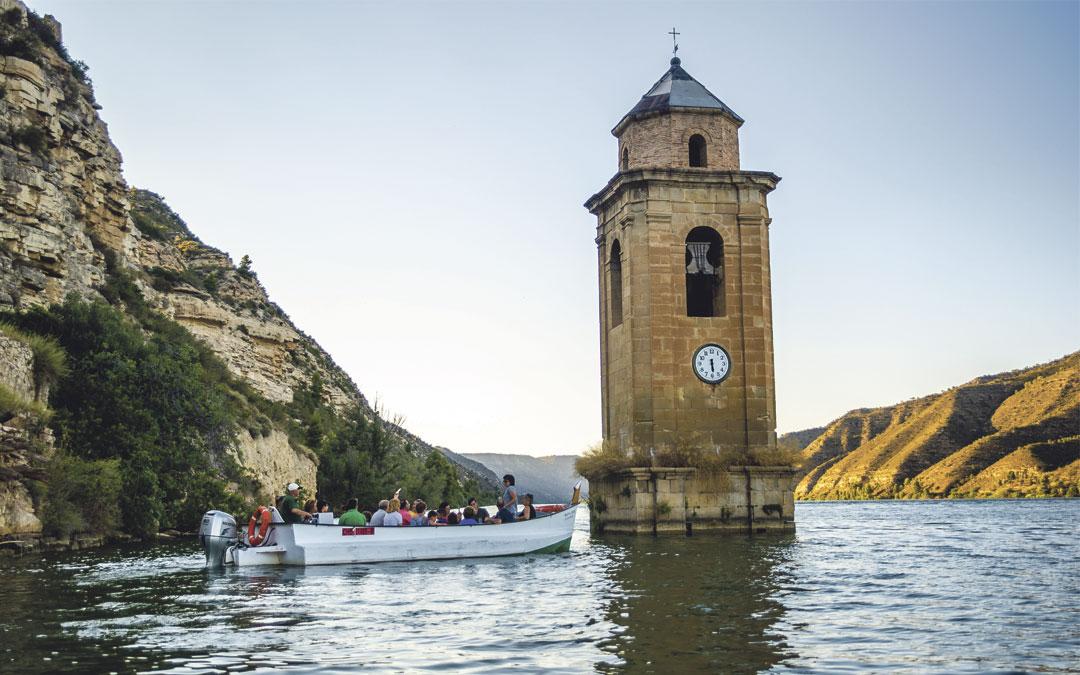 Ver de cerca el campanario del pueblo viejo de Fayón, el único elemento que no está sumergido bajo las aguas, es uno de los atractivos de los paseos en lläut de Fayón. Foto: Turismo Fayón