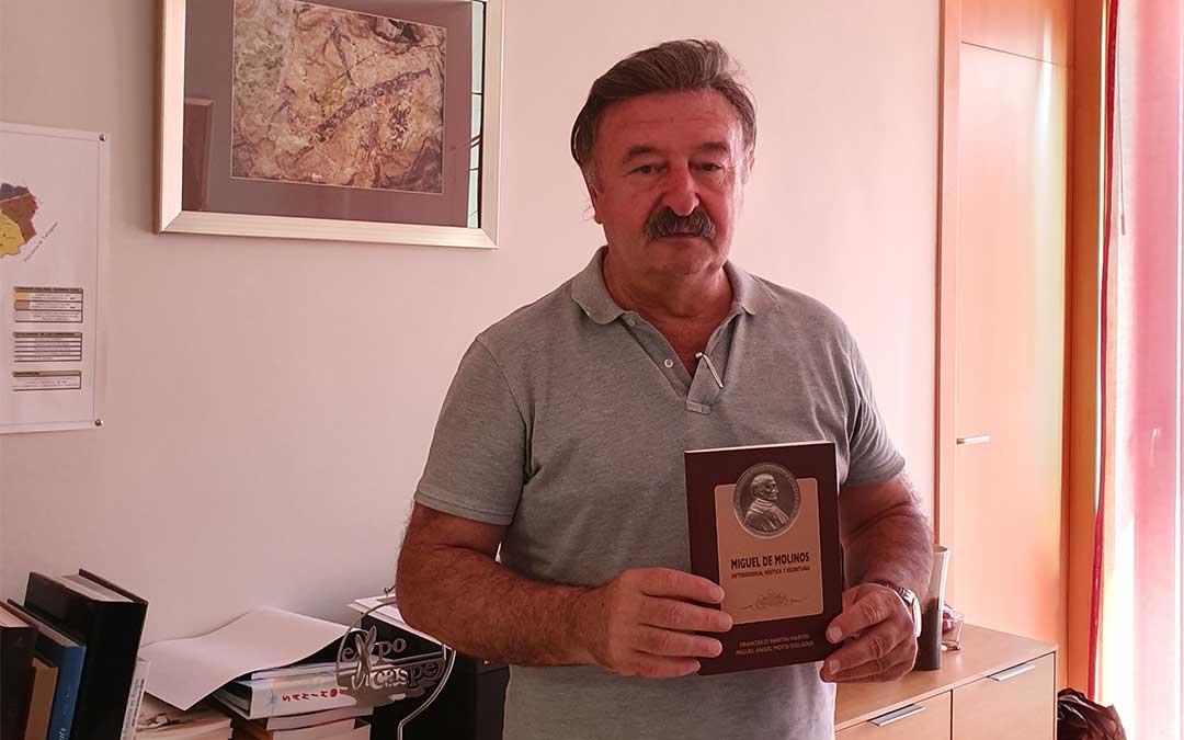 El presidente de la comarca de Cuencas Mineras, José María Merino, con el libro sobre la vida de Miguel de Molinos./ Cuencas Mineras.