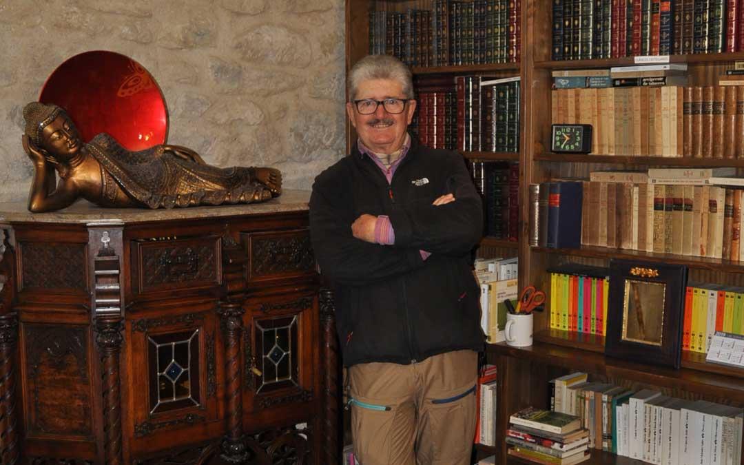 El alcalde de Torre del Compte, Alberto Díaz, junto a un Buda en un espacio de su biblioteca.