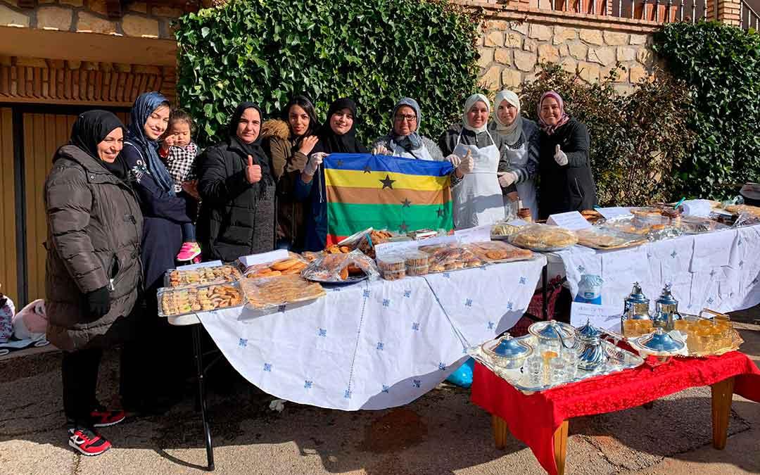 Las mujeres de uno de los puestos de comida del mercado lucen la bandera del Orgullo Rural./ Rural Mineras