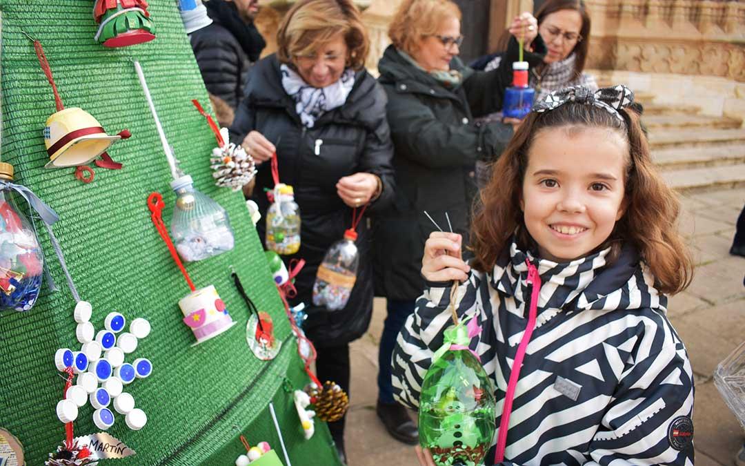 Una niña de sexto del Alejo Lorén decorando el árbol en Caspe.
