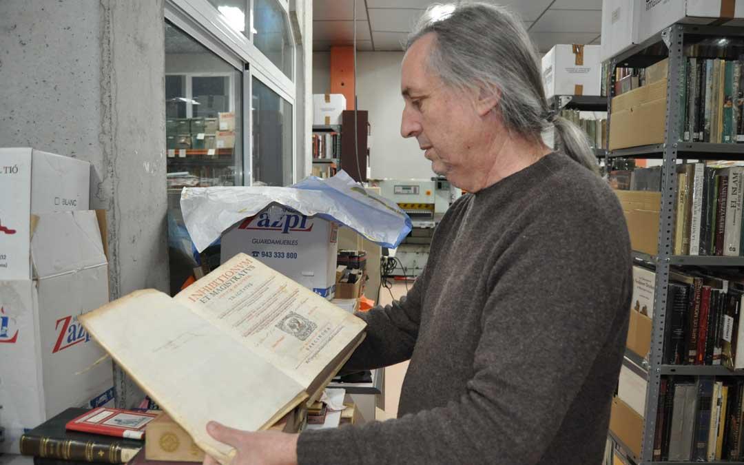 El librero calaceitano portando un ejemplar sobre derecho de la Corona de Aragón de 1604.