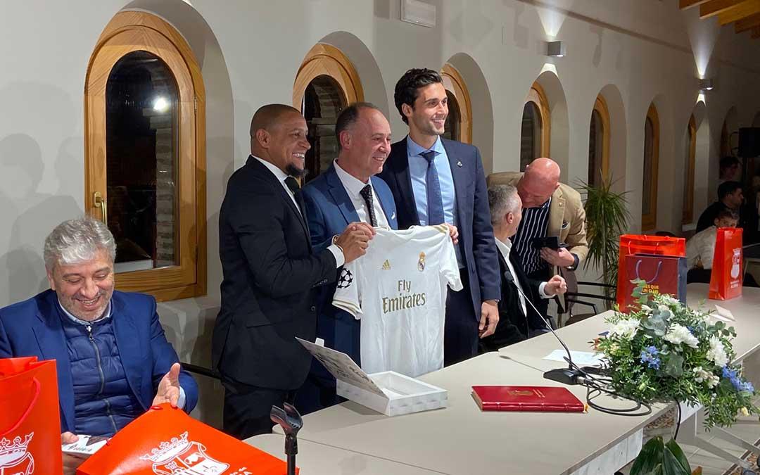 Miguel Iranzo, alcalde de la localidad, recibe una camiseta oficial del Real Madrid con la inscripción 'Alcorisa 2020'./ Alicia Martín