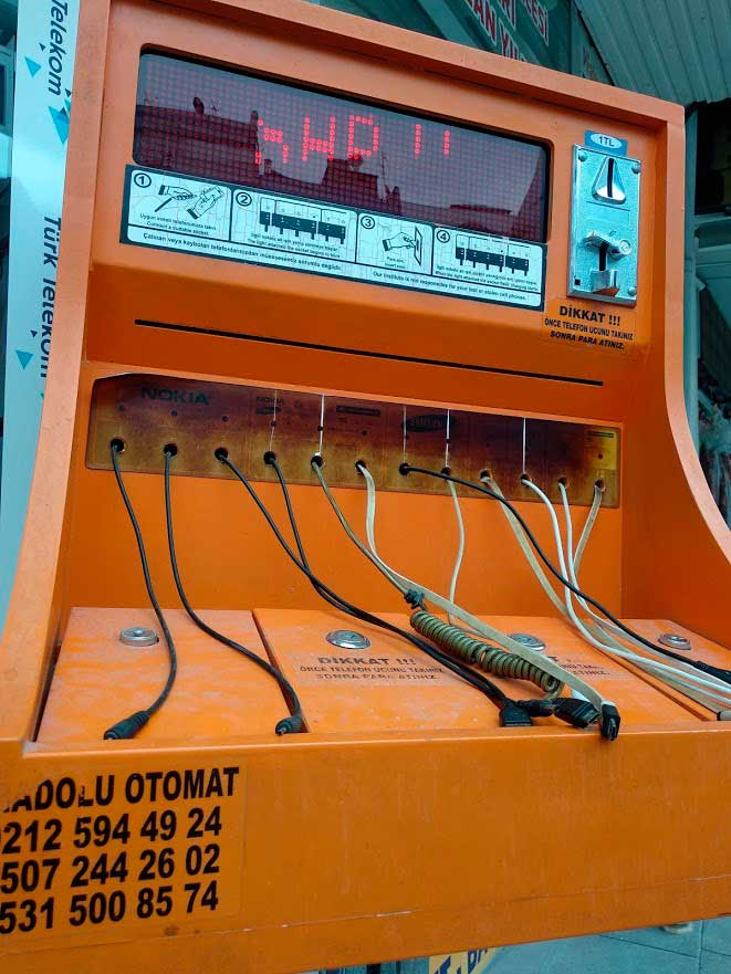 Un curioso cargador de teléfonos callejero. Se introducen monedas para pagar la carga y se guardan los móviles bajo llave./ La Comarca