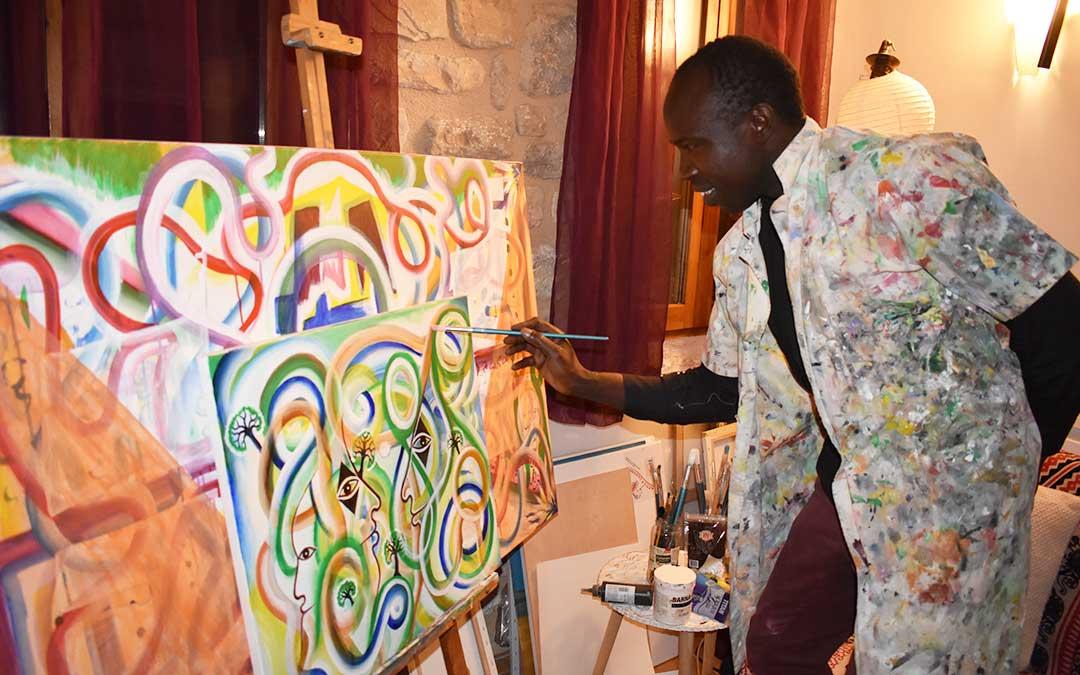 El artista Amadou Loum pintando uno de sus cuadros.