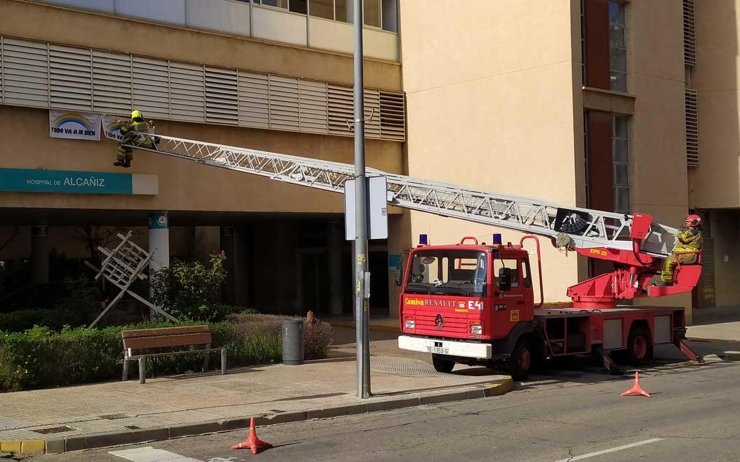 Los Bomberos de Alcañiz colocando carteles este miércoles en el Hospital de Alcañiz / Juan Peñalver