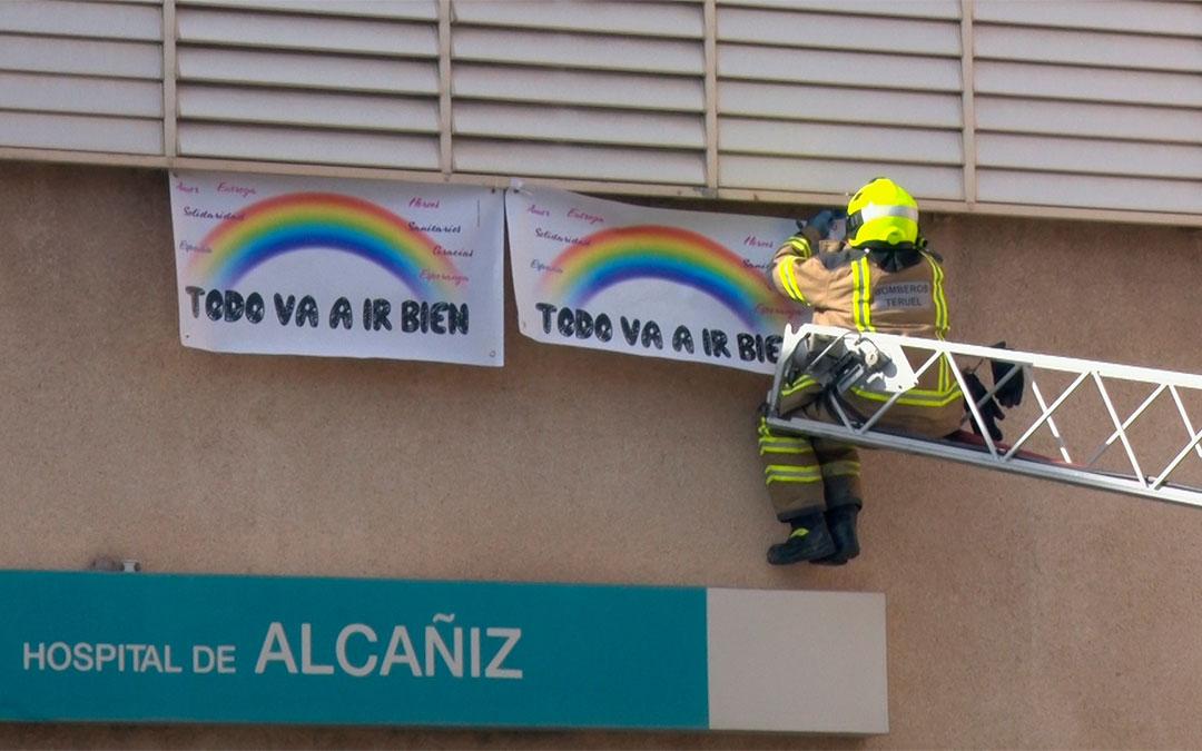 Los bomberos cuelgan los carteles en la fachada del Hospital Comarcal./ Juan Peñalver