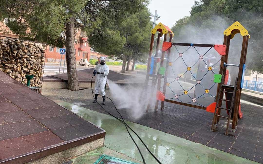 Un trabajador de la empresa Planas Martínez desinfectando un parque infantil en Caspe.