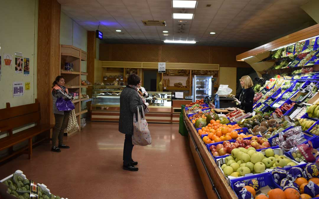 La dependienta de una frutería de Caspe atendiendo a varias clientas, respetando el aforo máximo permitido.