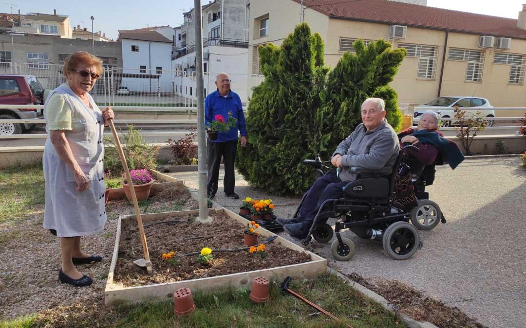 Usuarios de la residencia Guadalope de Mas de las Matas, plantando las macetas donadas por Agrojardín. / Ayto. Mas de las Matas