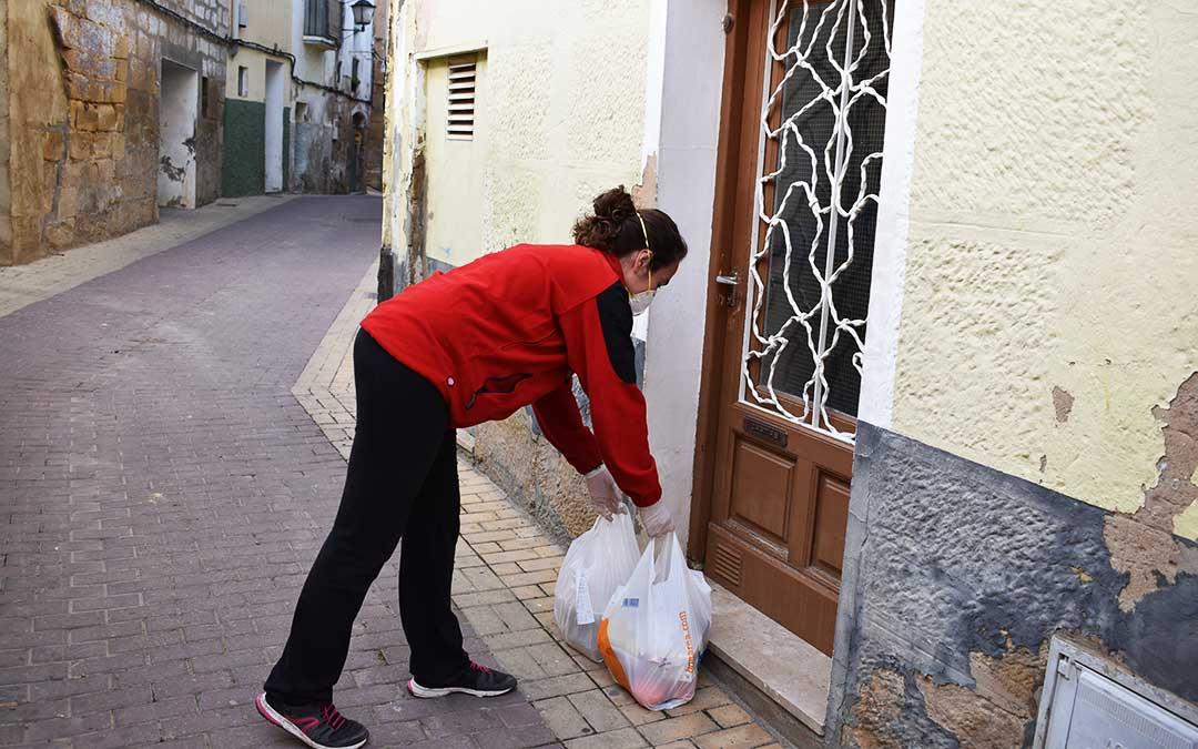 Una voluntaria entrega en la puerta de un usuario unas compras.