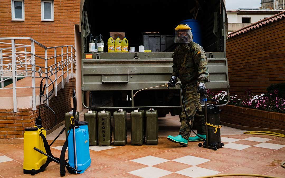 Un miembro del Ejército de Tierra cogiendo los utensilios de desinfección. Imagen: Césareo Larrosa.