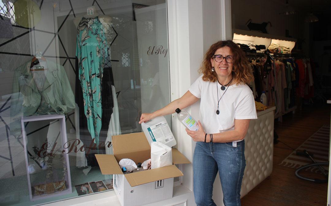 Cristina Foz, en la puerta de su tienda El Ropero con los preparativos. / L. Castel