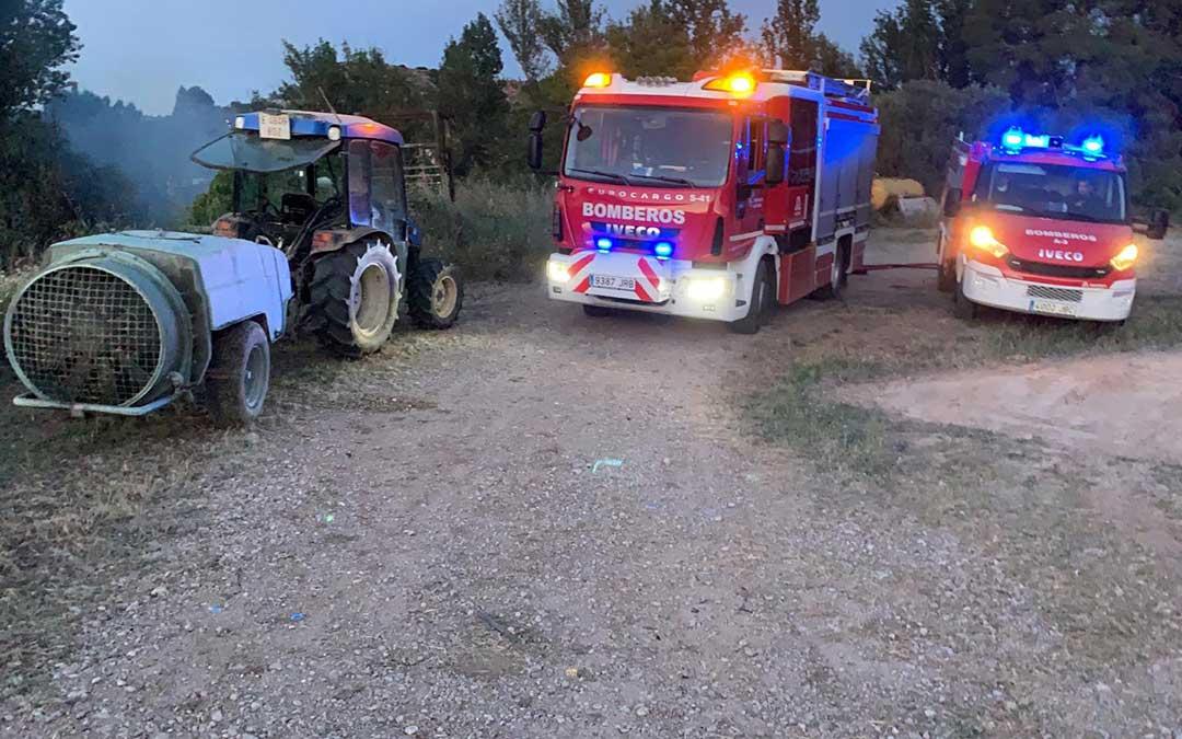 La desbrozadora que causó el incendio y los bomberos, en la zona afectada junto al río Guadalope./ L.C.