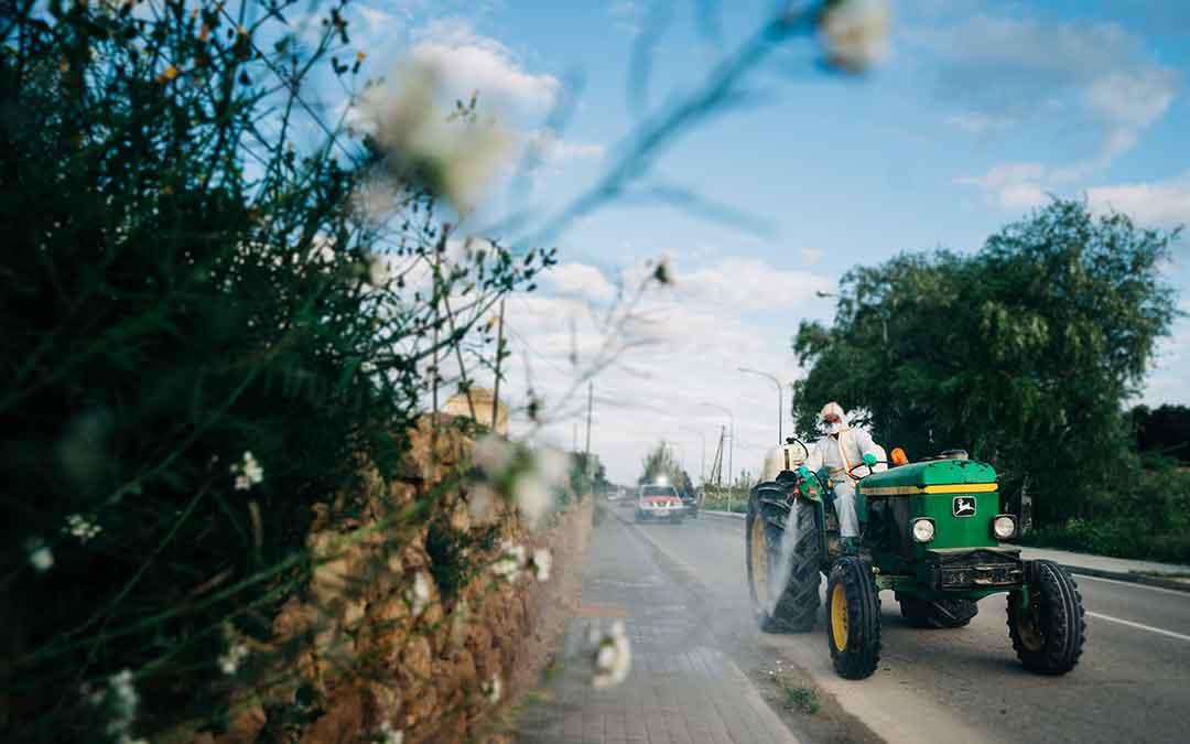 Un voluntario con su tractor realizando labores de desinfección. Imagen: Cesáreo Larrosa.