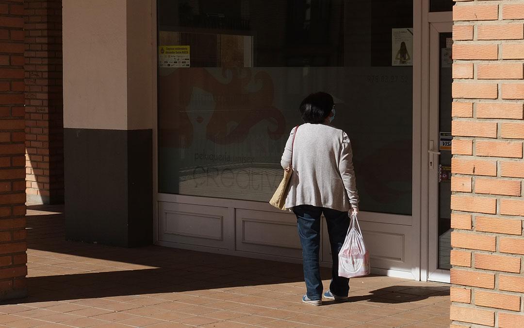 Una mujer en Alcañiz delante de un establecimiento cerrado después de salir a hacer la compra./ A.M.
