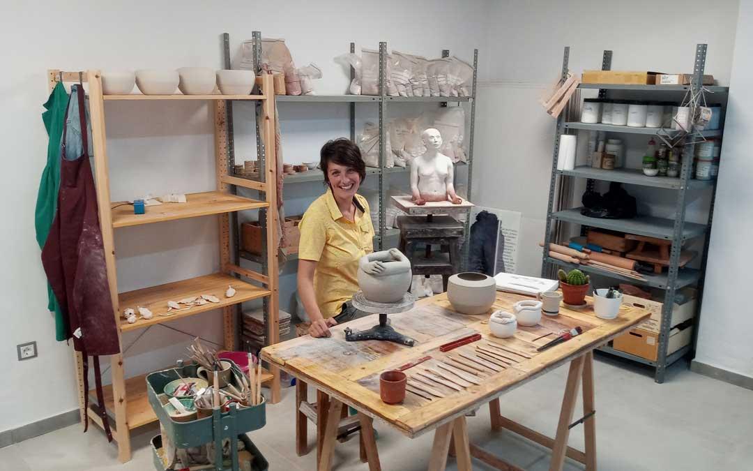 Malia Pérez, en su taller-laboratorio en Oliete con sus creaciones. Al fondo, el boceto de 'Moradoras de la tierra'. / Archivo personal