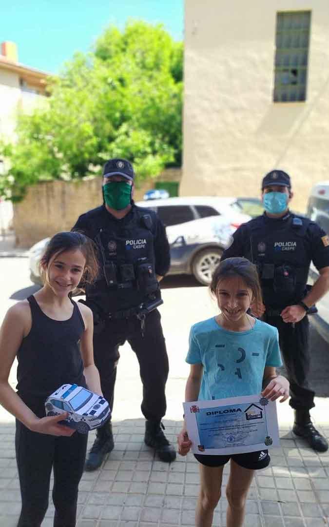 Dos niños con sus coches hechos de papel junto a dos policías locales en Caspe.