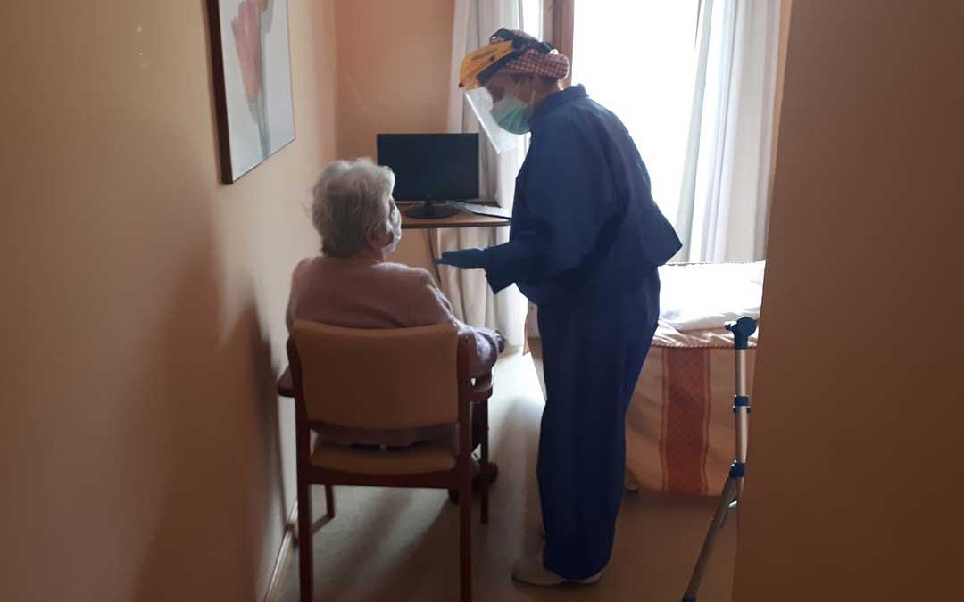 Una de las trabajadoras de la residencia de Valderrobres equipada con un traje de máxima protección atendiendo a una anciana en su habitación en el centro