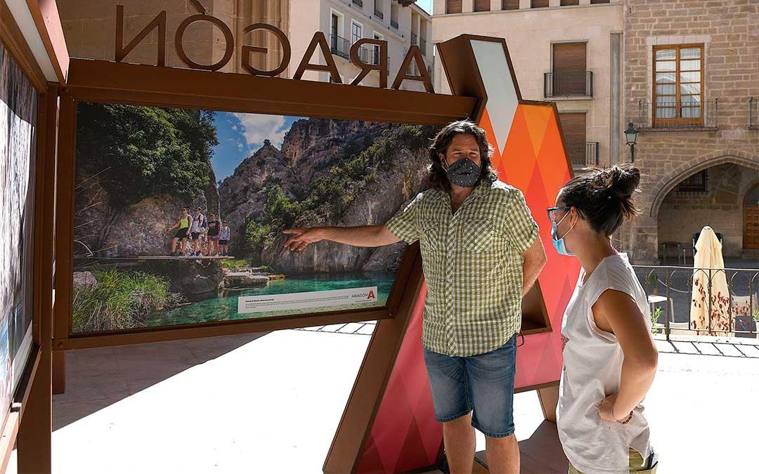 Visita del concejal de Turismo, Jorge Abril, y la técnica de la DG de Turismo, Marta Güell, a la exposición 'Este verano salimos juntos' en la Lonja de Alcañiz./ Ayto. de Alcañiz