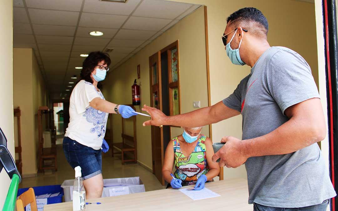 Una funcionaria municipal entrega un sobre con mascarillas y un folleto de recomendaciones a un vecino de Caspe./ Pilar Sariñena