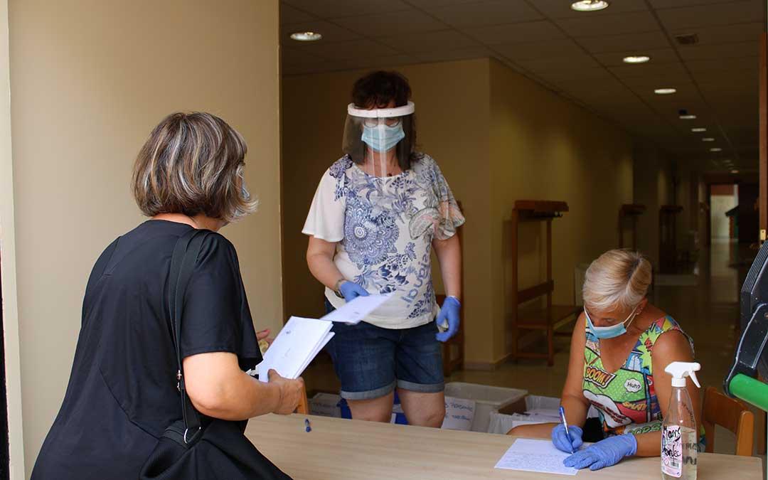 Personal municipal entregando mascarillas a una vecina.