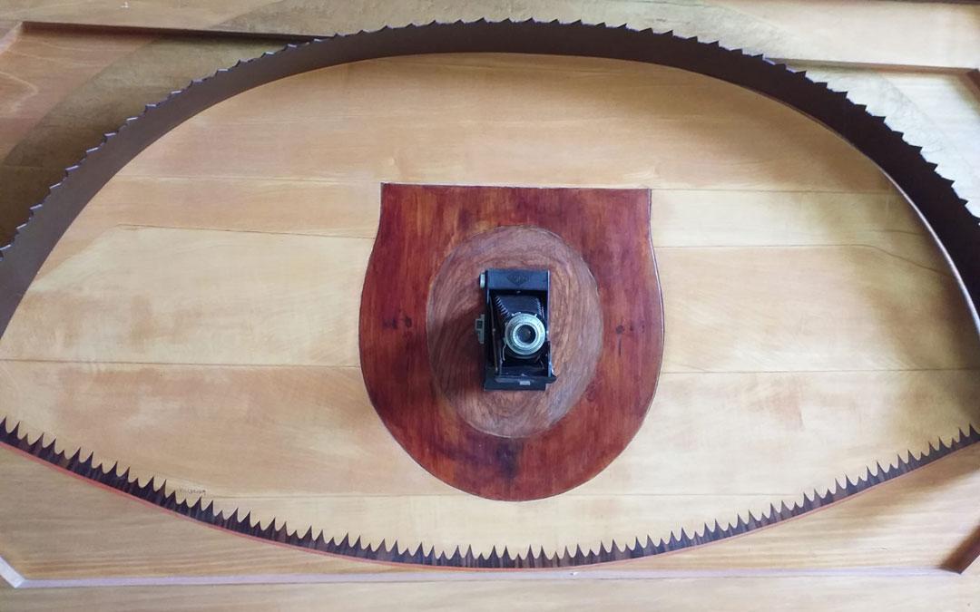 Pieza reversible con una sierra, una tapa de wáter y una cámara incrustadas.