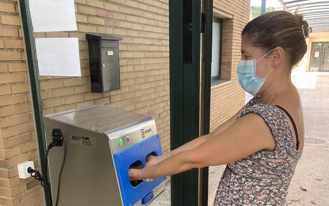 Marisé Moreno, directora del IES Damián Forment, muestra el funcionamiento del dispositivo higienizante de manos. / Ayto. Alcorisa