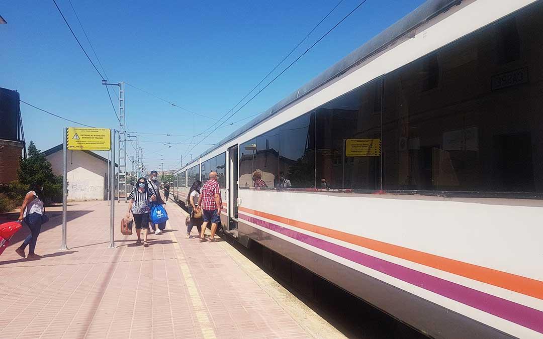 Varios vecinos de la zona de Caspe subiendo y bajando del tren con mascarilla.