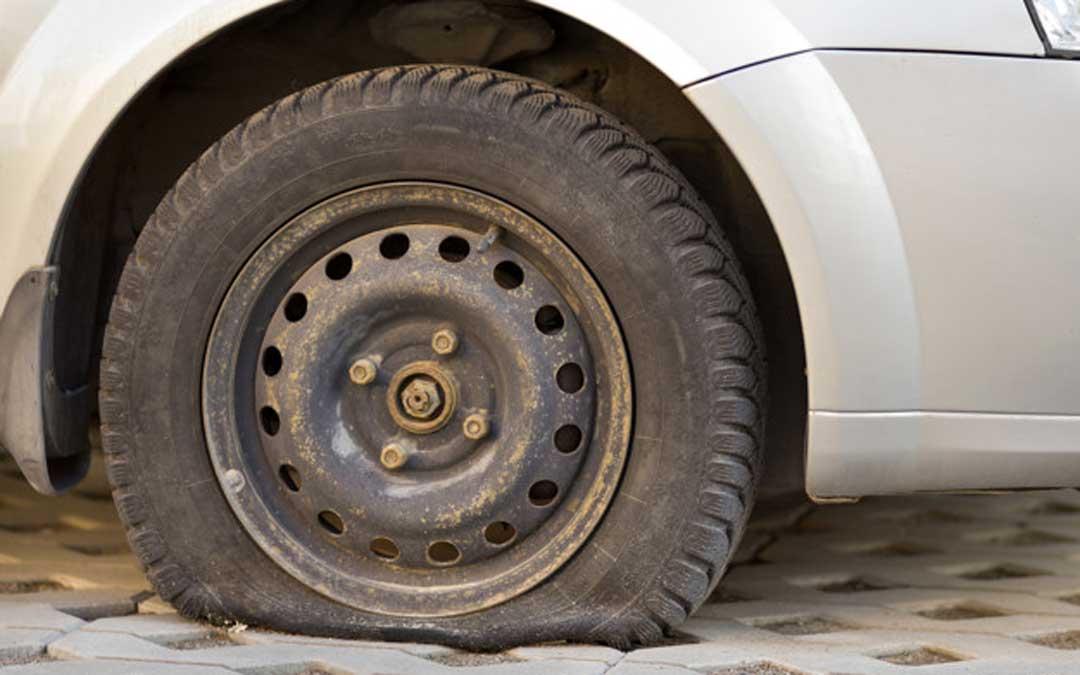 Foto de archivo de un coche con la rueda pinchada / Freepik