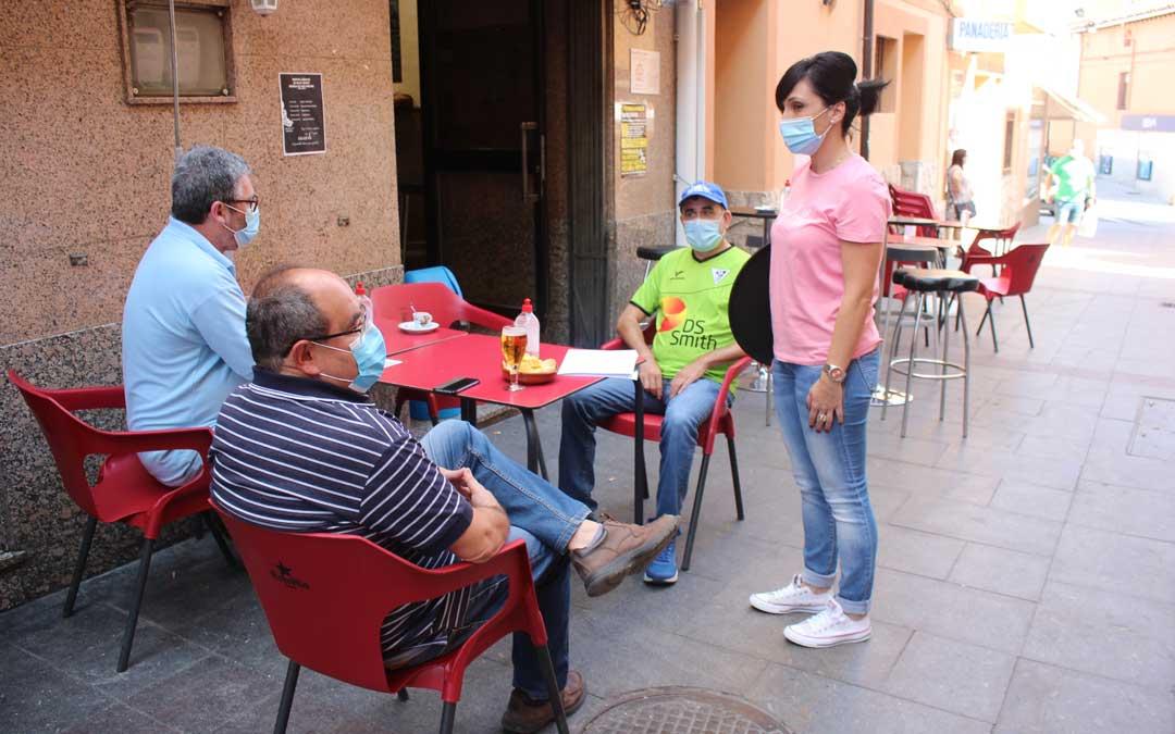 Turia Serrano atendiendo a unos clientes en su bar con los aforos al 50% y con distancia interpersonal / L. Castel