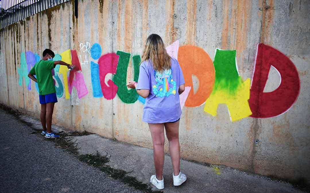 Dos jóvenes terminando el mural.