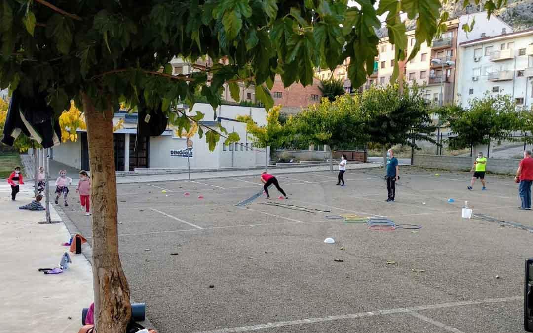 Adultos y niños realizando actividad deportiva en uno de los pueblos de la comarca