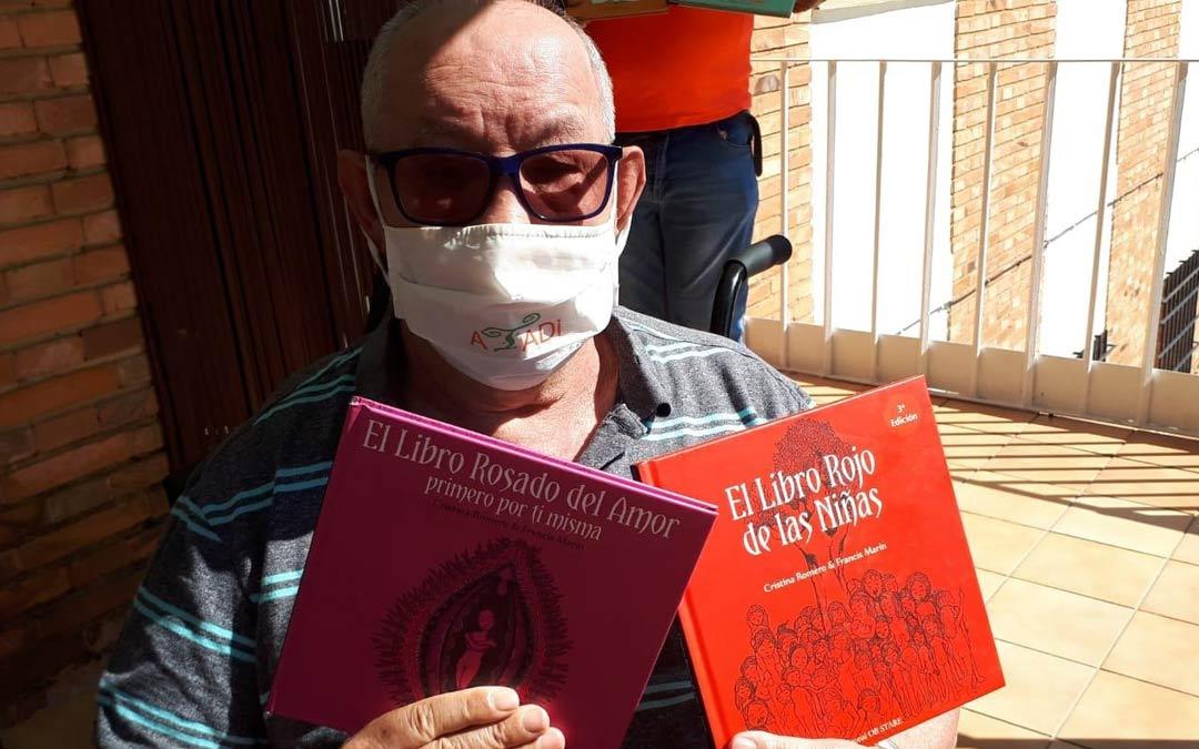 Un usuario de ATADI sujeta algunos de los libros entregados por el Ayuntamiento./M. Santos