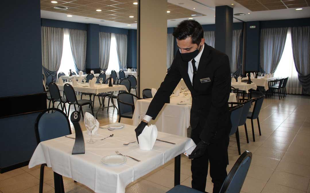 Un camarero preparando una de las mesas del salón destinado exclusivamente a los equipos en el Hotel Ciudad de Alcañiz